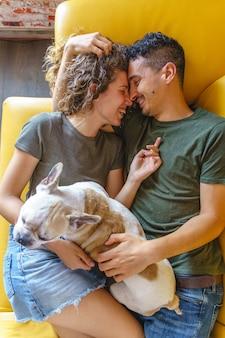 Casal beijando e fazendo cócegas no bulldog em casa no sofá. vista superior horizontal brincando com animal de estimação