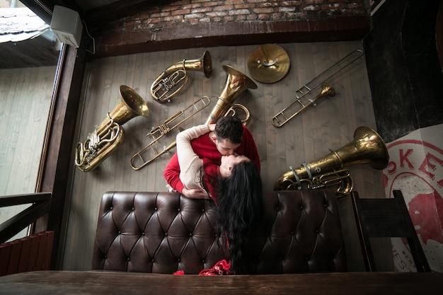 Casal beijando entre instrumentos musicais