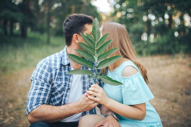 Casal beijos na floresta, sentado em um galho de árvore e fecha com uma folha