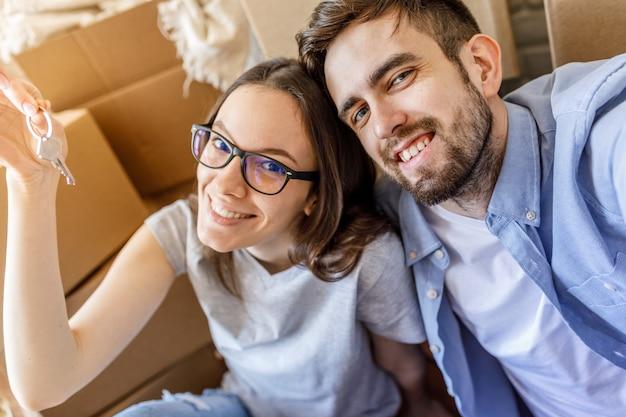 Casal bem sucedido sorridente com chaves planas Foto Premium