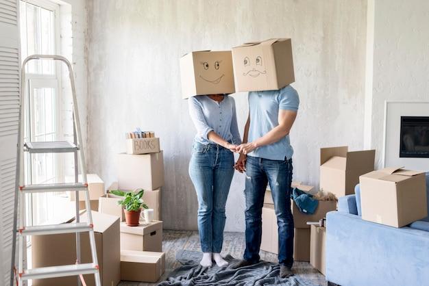 Casal bobo com caixas sobre as cabeças de mãos dadas no dia da mudança