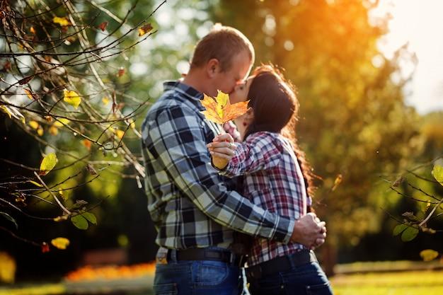 Casal bonito ao ar livre no outono. homem jovem, e, mulher, beijando