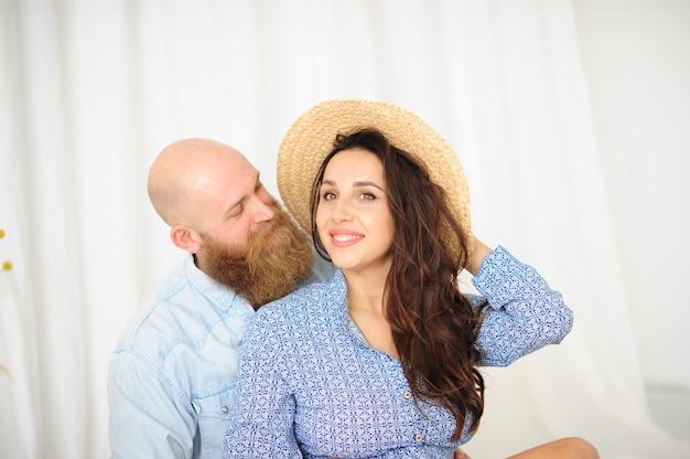 Casal bonito com a mulher de chapéu em um fundo de cortina branca.