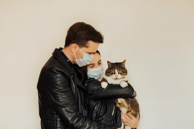Casal bonito com máscaras médicas. menina segurando nas mãos seu gato sério