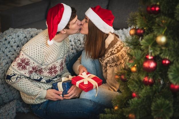 Casal bonito com presentes de natal beijando