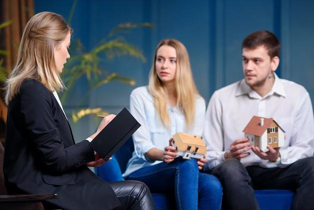 Casal bonito concentrado na reunião com o designer no fundo da parede azul.