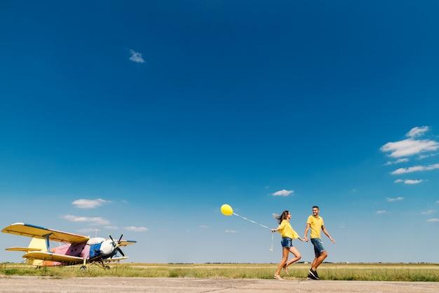 Casal bonito correndo e de mãos dadas. em campo e avião. dominando as cores azuis e amarelas.