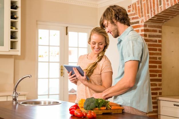 Casal bonito cozinhar e usar tablet na cozinha