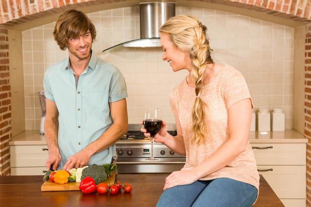 Casal bonito, desfrutando de um copo de vinho e cortar legumes na cozinha