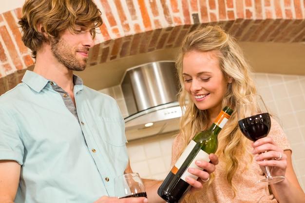 Casal bonito, desfrutando de um copo de vinho e lendo a garrafa na cozinha