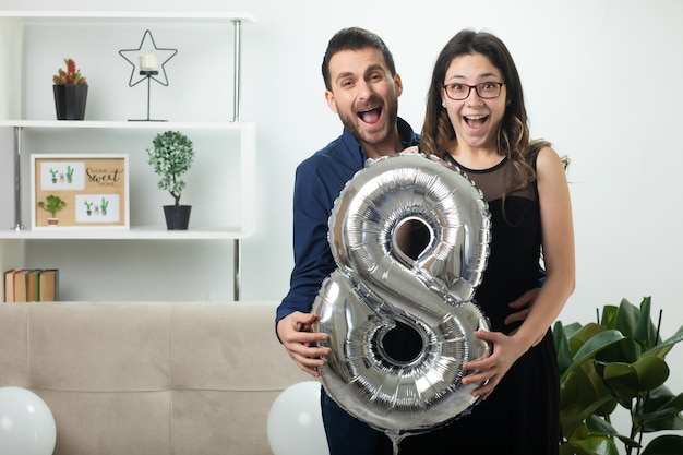 Casal bonito e alegre segurando um balão em forma de oito em pé na sala de estar em março, dia internacional da mulher