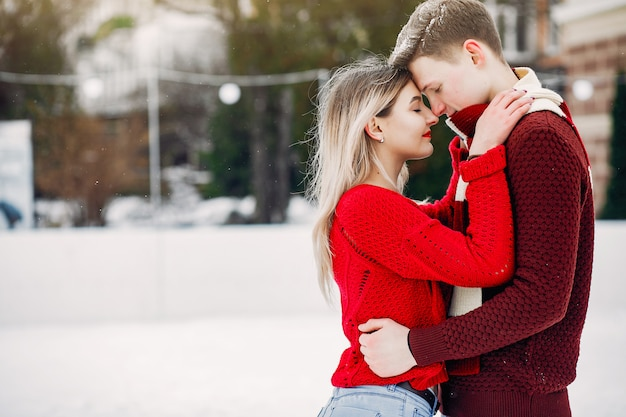 Casal bonito e amoroso um suéteres vermelhos em uma cidade de inverno