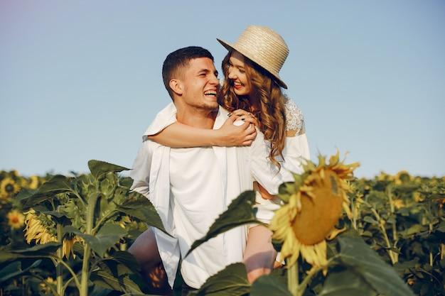 Casal bonito e elegante em um campo com girassóis
