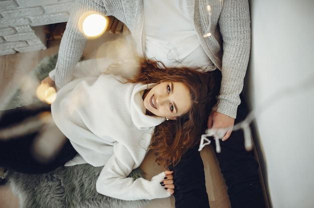 Casal bonito em casa em uma camisola quente