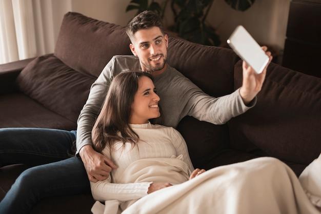 Casal bonito em casa no modelo de sofá