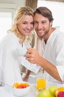 Casal bonito em roupões tomando café da manhã juntos, sorrindo para a câmera