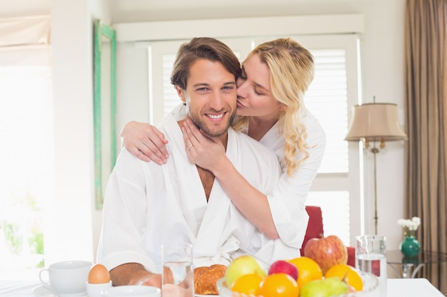 Casal bonito em roupões tomando café da manhã juntos
