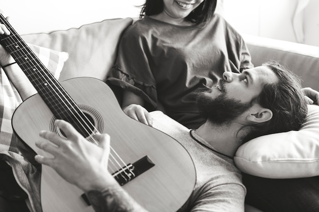 Casal bonito em um namorado de sofá tocando um conceito de música e amor de guitarra