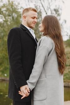 Casal bonito em um parque. senhora com um casaco cinza. pessoas no cais.