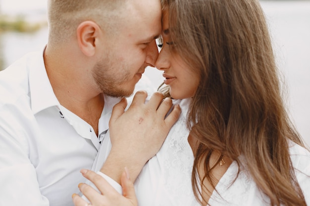 Casal bonito em um parque. senhora de camisa branca. pessoas no cais.