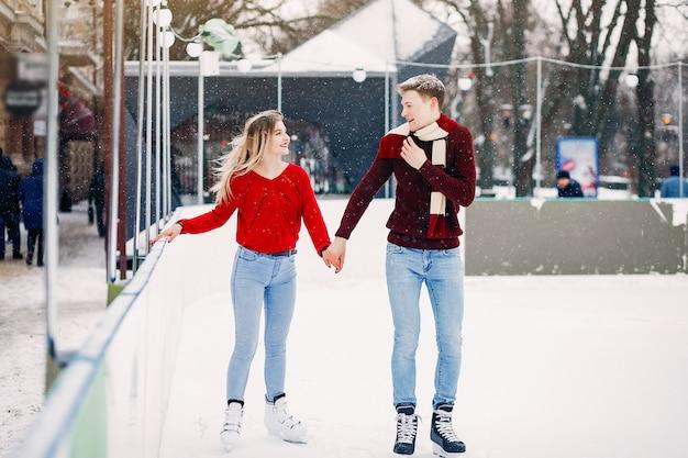 Casal bonito em um suéter vermelho se divertindo em uma arena de gelo