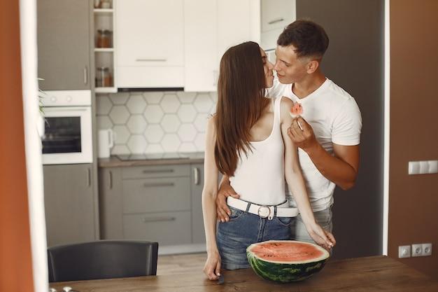 Casal bonito em uma cozinha. senhora em uma camiseta branca. pares em casa comendo melancia.