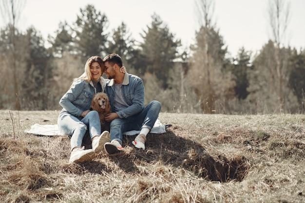 Casal bonito em uma roupa jeans em um campo de primavera