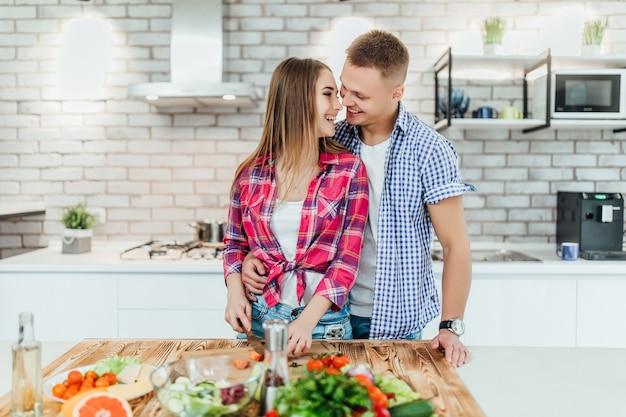 Casal bonito jovem romântico cozinhando na cozinha moderna branca com legumes e frutas na mesa.