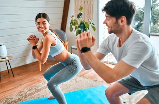 Casal bonito mulher coreana e homem musculoso em roupas esportivas fazer exercícios de agachamento em esteiras na sala de estar em casa. estilo de vida saudável, ioga, esportes, fitness.