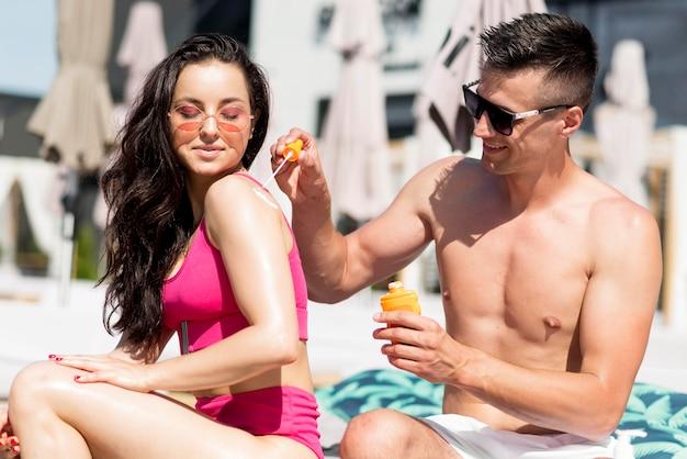 Casal bonito na praia com protetor solar