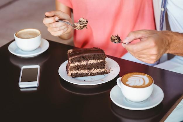 Casal bonito num encontro partilhando um pedaço de bolo de chocolate