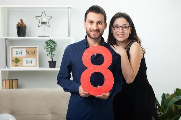 Casal bonito sorridente segurando oito figuras vermelhas em pé na sala de estar em março, dia internacional da mulher