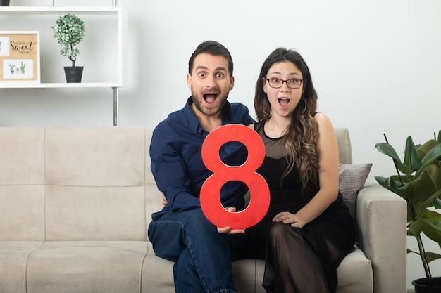 Casal bonito surpreso segurando o número oito vermelho sentado no sofá na sala de estar em março, dia internacional da mulher
