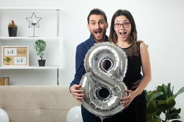 Casal bonito surpreso segurando um balão em forma de oito em pé na sala de estar em março, dia internacional da mulher