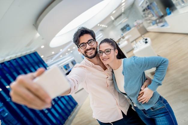 Casal bonito tomando auto-retrato e se abraçando em pé na loja de tecnologia. novo conceito de tecnologias.