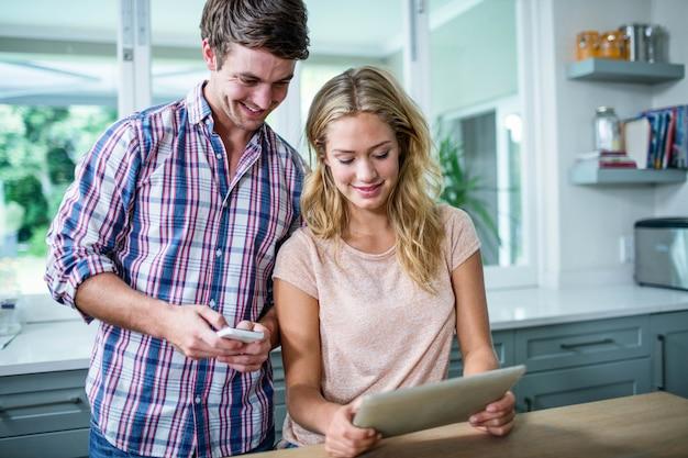 Casal bonito usando computador tablet na cozinha em casa