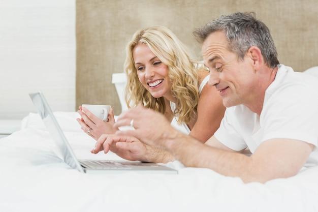Casal bonito usando laptop na cama no quarto deles
