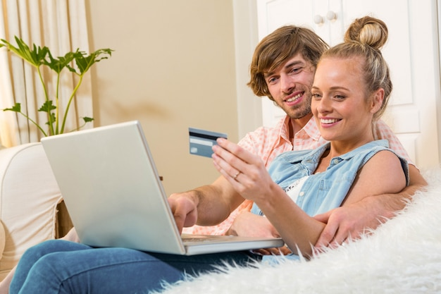 Casal bonito usando laptop para fazer compras on-line sentado no sofá na sala de estar