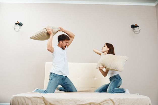 Casal brigando de travesseiro no quarto