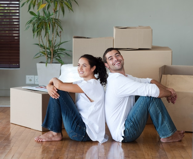 Casal brilhante com caixas de desembalagem se movendo para uma nova casa