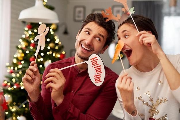 Casal brincalhão com máscaras de natal