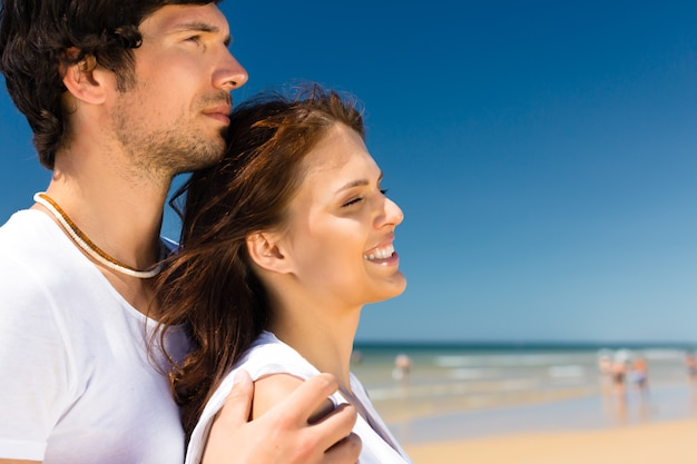 Casal brincalhão na praia do oceano, aproveitando as férias de verão, ele a abraça