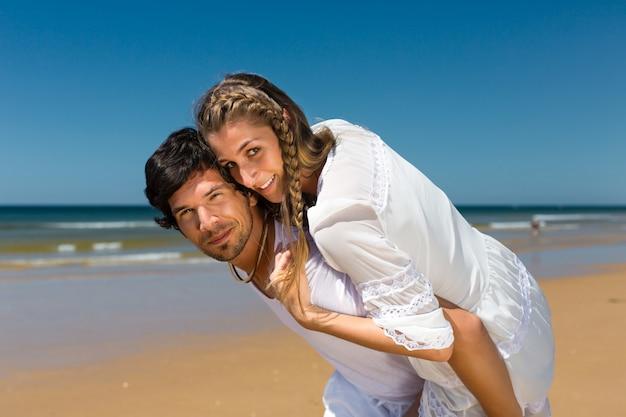 Casal brincalhão na praia do oceano, aproveitando as férias de verão, o homem está carregando a mulher nas costas