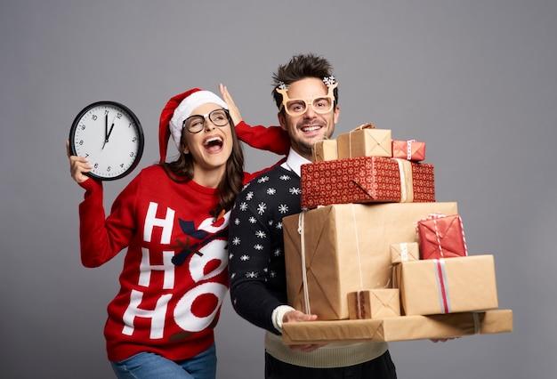 Casal brincalhão segurando uma pilha de presentes de natal