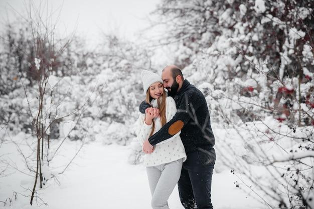 Casal brincando com a neve na floresta.