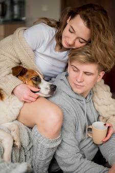 Casal brincando com cachorro em casa