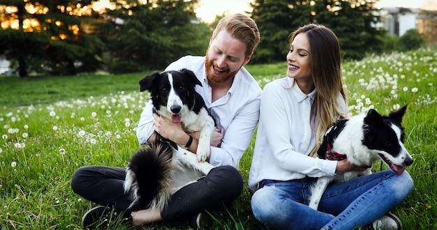 Casal brincando com cachorros no parque