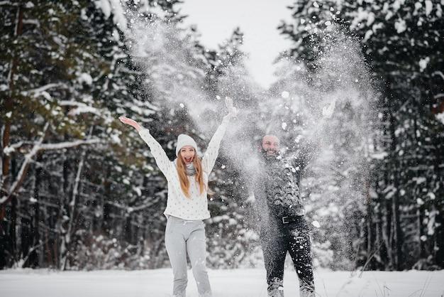 Casal brincando com neve na floresta