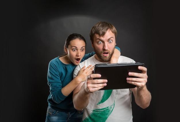Casal brincando com tablet na rua