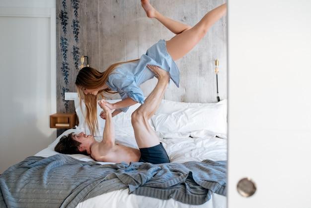 Casal brincando e se divertindo em casa na cama